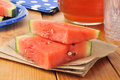 Watermelon slices fresh on a wooden table with a pitcher of iced tea Stock Images