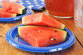 Watermelon slices on picnic plates with a pitcher of iced tea Stock Photos