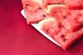 Watermelon slices still life of red on a plate and red tablecloth Stock Photography