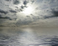Waterscape sun behind cloudy sky Royalty Free Stock Images