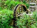 Waterwheel a weathered wooden near a stone wall in a village of yunhe country lishui city zhejiang province china Stock Image