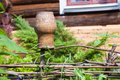 Wattle fence with old clay pot and log house Royalty Free Stock Photo