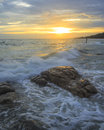 Wave crashes down onto the rocks waves hitting round and splashing with sunset Stock Image