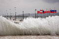 Wave crashing on the pier tsunami like big waves of port of itea greece Stock Images
