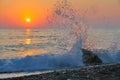 Wave crashing rock creates water swirl sunset Royalty Free Stock Photo