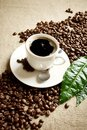 Wave diagonally made of coffee beans with cup of frothy coffee with leaf Royalty Free Stock Photo