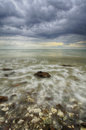 Wave hitting the rock with dramatic dark clouds during the evening and low tide water Royalty Free Stock Photo
