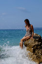 Wave splash woman sitting on a rock on the sea shore with feet in the water splashing Stock Photo