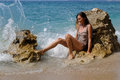 Wave splash woman sitting on a rock on the sea shore splashing Royalty Free Stock Image
