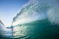 Wave surfer behind crashing water swimming blue morning hollow with unidentified from a perspective Stock Image
