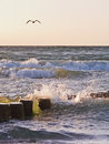 Wavebreakers in storm and stormy sea at sunset Stock Images