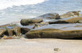 Waves approaching sandy beach with large boulders Royalty Free Stock Photo