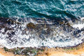 Waves crashing breaking on the rocks. Drone aerial sea surface view Royalty Free Stock Photo