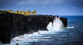 Waves crashing on volcanic cliffs crash along the black lava rock in the hawaiian volcanoes national park this view is at the end Royalty Free Stock Image