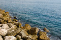 Waves of the mediterranean sea water crushing into reddish rocks Royalty Free Stock Photo