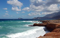 Waves on red rock sea shore with mountains and blue sky Royalty Free Stock Photo