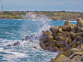 Waves and rocks on the quay crashing into Royalty Free Stock Photo