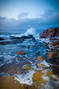 Waves on rocks towards beach with Stock Photography