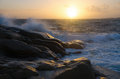 Waves on rocks towards beach with at sundown Stock Photo