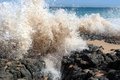Waves splashing on basalt rocks at ocean beach bunbury western australia the ancient dark send sandy spray high into the air a Royalty Free Stock Image