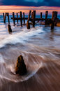 Waves swirl around pier pilings in the delaware bay at sunset s seen from beach cape may new jersey Stock Image