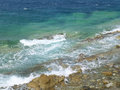 Waves of turquoise blue Aegean Sea crashing on the rocks at Mykonos Royalty Free Stock Photo