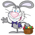 Waving gray bunny with easter eggs and basket Stock Photos