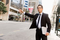 Waving for a taxi in city businessman trying to catch business cuty district Stock Photo