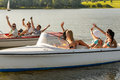 Waving young friends sitting in motorboats enjoying summertime Royalty Free Stock Photos
