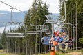 Waving young people sitting on chairlift going through forest Royalty Free Stock Images