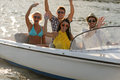 Waving young people in sunglasses sitting in motorboat summertime Royalty Free Stock Photos