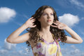 Wavy brunette with colored dress with hands in the hair Stock Image
