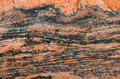 Wavy texture of granite stone red tint and dark stripes.
