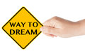 Way to dream sign traffic in woman s hand on a white background Royalty Free Stock Images