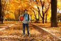 On the way to play basketball handsome smiling black boy years old standing in autumn park under maple trees with orange ball Stock Image