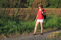 On the way woman with hat and backpack standing road in countryside Stock Image