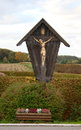 Wayside cross a wooden with fields in the background Stock Photos