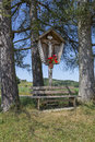 Wayside shrine and bench between tall trees bavaria germany Royalty Free Stock Images