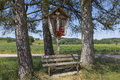 Wayside shrine and bench between tall trees bavaria germany Stock Image