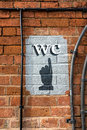 Wc sign a painted on a red brick wall Stock Photos