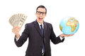 Wealthy businessman holding money and a globe isolated on white background Stock Photo