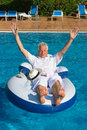 Wealthy man cheering and relaxing in own swimming pool Stock Photo
