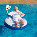 Wealthy man relaxing in own swimming pool Royalty Free Stock Image
