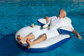 Wealthy man relaxing in own swimming pool Royalty Free Stock Photos