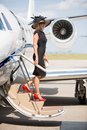 Wealthy woman disembarking private jet at airport side view of terminal Royalty Free Stock Photos