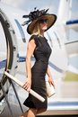 Wealthy woman getting off private jet side view portrait of at airport terminal Stock Photography