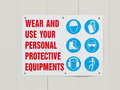 Wear personal protective equipments signboard on hoarding outside construction site reminding workers to and use Royalty Free Stock Photos
