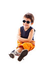 Wearing sunglasses child sitting in studio and smiling Stock Photos