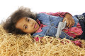 Weary with gun a young sleepy looking cowgirl holding her across her chest while laying in the hay Stock Images