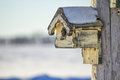 Weather beaten birdhouse in winter with snow on roof Stock Photography
